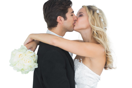 Nice bride embracing and kissing her husband holding a white bouqet photo