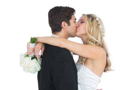 Happy attractive married couple posing kissing each other holding a bouquet photo