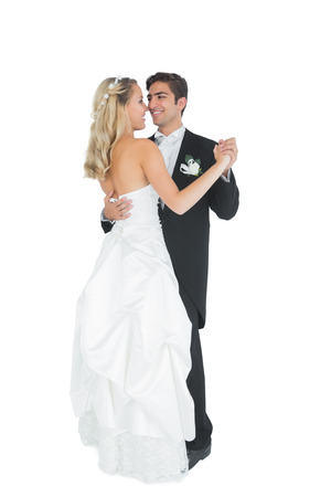 Cute young married couple dancing viennese waltz on white background photo