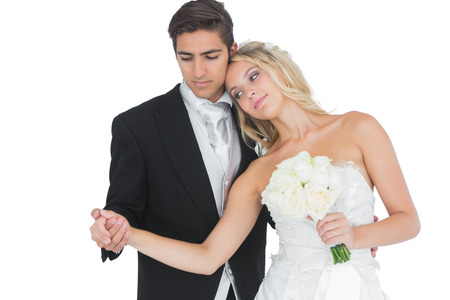 Young beautiful bride posing with her husband holding a white bouquet photo