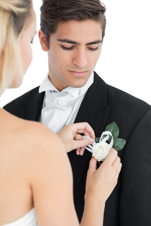 pinning: Young bride pinning a flower on her husbands suit on white background Stock Photo