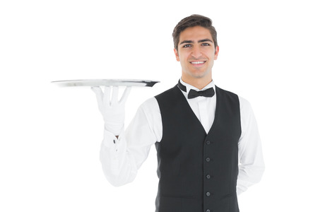 Attractive waiter presenting an empty tray smiling at camera photo