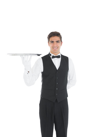 Cheerful young waiter showing an empty silver tray smiling at camera photo