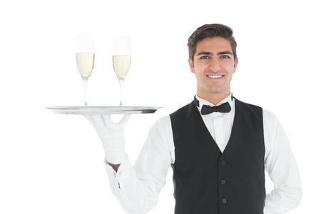 Smiling attractive waiter holding a tray with champagne glasses on it smiling at camera photo