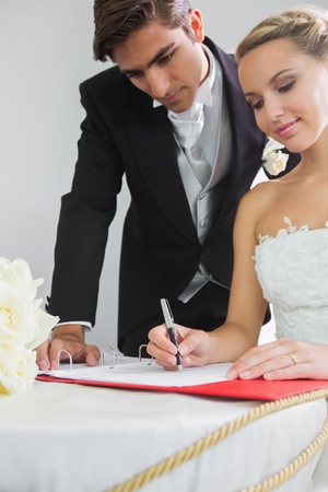 Young smiling bride signing wedding contract being watched by her husband photo