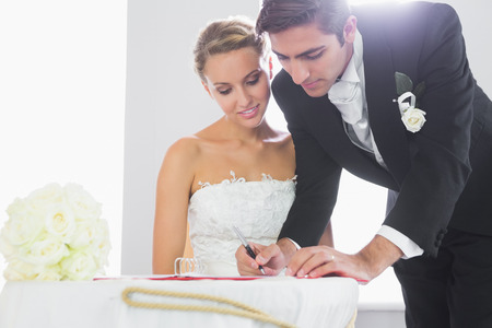 Handsome bridegroom signing wedding contract at desk photo