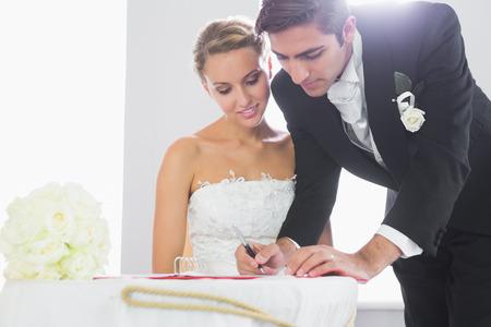 beautiful brunette: Handsome bridegroom signing wedding contract at desk
