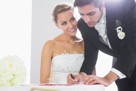Beautiful bride watching her handsome husband signing wedding contract photo