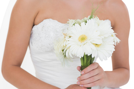 Mid section of young bride holding a bouquet on white background Stock Photo