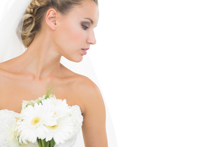 tied down: Thoughtful pretty bride holding a bouquet looking down on white background