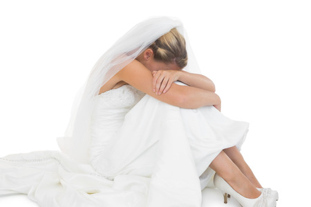 Unhappy blonde bride sitting on floor hiding her face