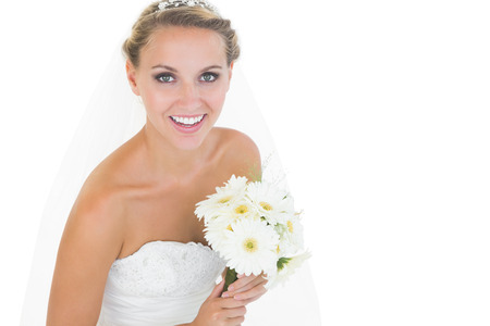 Side view of cheerful young bride holding a bouquet smiling at camera photo