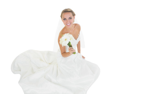 Cheerful young bride sitting on floor showing her bouquet smiling at camera photo