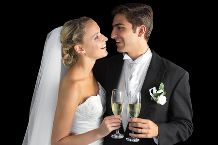 Cheerful married couple holding champagne glasses on black background photo