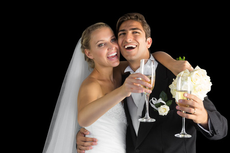 Cheerful happy married couple laughing on black background photo