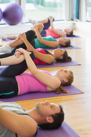 Sporty people doing the supine wind release posture at yoga class photo