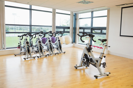 gym room: Spinning exercise bikes in a bright gym room Stock Photo