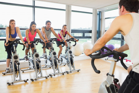 Cropped man teaching spinning class to four people in gym photo
