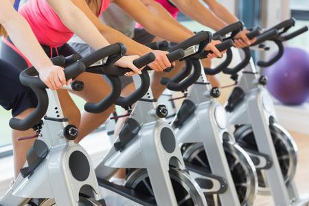 actividad fisica: La secci�n media de cuatro personas que se resuelven en clase de spinning en el gimnasio Foto de archivo