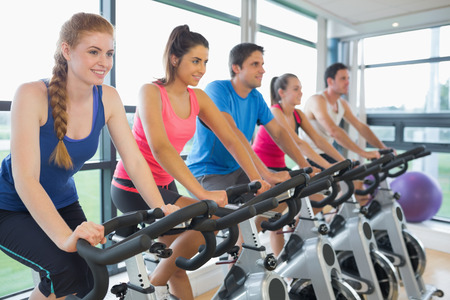 Determined five people working out at spinning class in gym photo