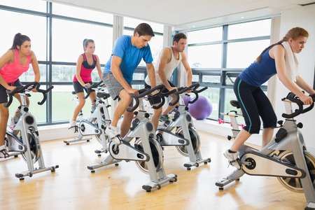 Determined five people working out at spinning class in gym Фото со стока