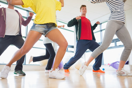 zumba: Classe Fitness e istruttore facendo esercizio di pilates in camera luminosa