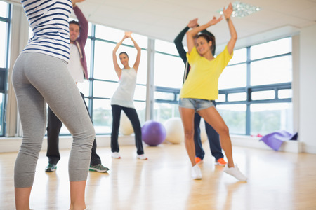 Fitness class and instructor doing pilates exercise in bright room photo