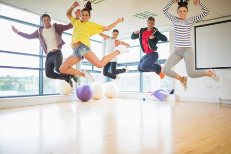 Group portrait of young fit people jumping in bright exercise room photo