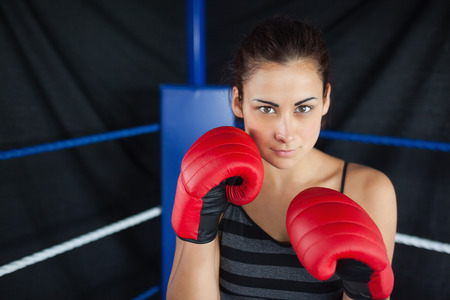 Portrait of a beautiful young woman in red boxing gloves in the ring photo