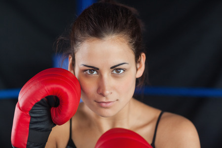 Close-up portrait of a beautiful young woman in red boxing gloves in the ring photo