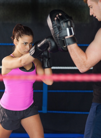 Determined female boxer practicing in the boxing ring photo