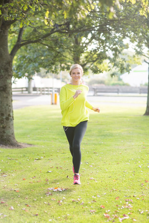 Active smiling blonde jogging towards camera in a park on a sunny day photo