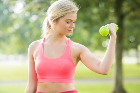 woman muscle: Active smiling blonde lifting dumbbells in a park on a sunny day Stock Photo