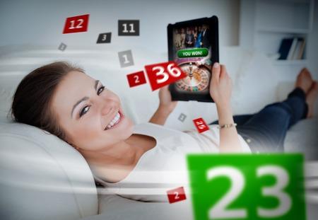 ruleta de casino: Mujer tumbada en el sofá y los juegos de azar en la tableta con números holográficas a su alrededor