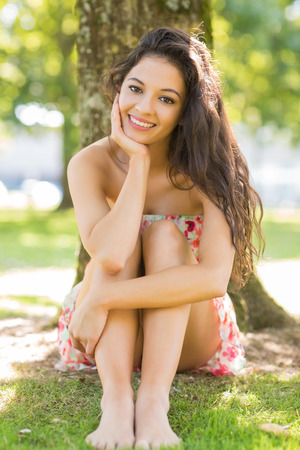 Stylish happy brunette sitting under a tree in a park on a sunny day photo