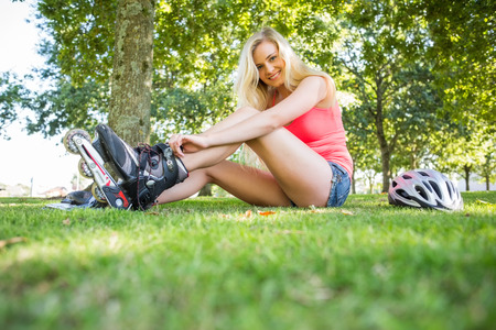 Casual smiling blonde putting on roller blades in a park on a sunny day photo