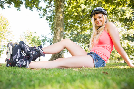 Casual smiling blonde wearing roller blades and helmet in a park photo