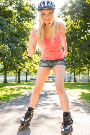 Casual cheerful blonde inline skating in a park photo