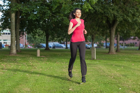 Beautiful woman running in a park while listening to music photo