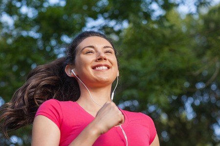 Joyful sporty woman jogging in a park listening to music photo