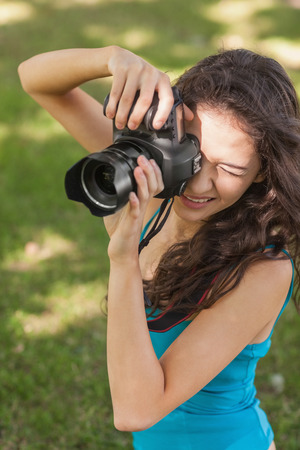 High angle view of brunette young woman taking a picture on a lawn photo
