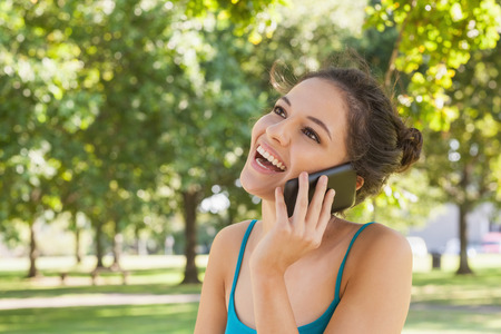Happy young woman phoning with her smartphone sitting in a park photo