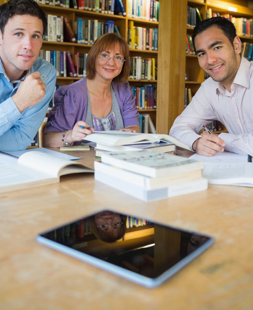 Portrait of three mature students studying together in the library photo