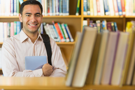 Portrait of a smiling mature student with tablet PC against bookshelf in the library photo
