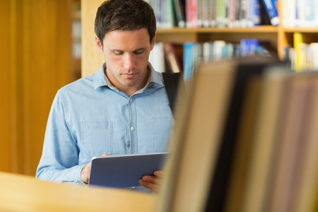 Concentrated mature student using tablet PC against bookshelf in the library photo
