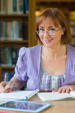 Close-up portrait of a smiling mature female student at desk in the library photo