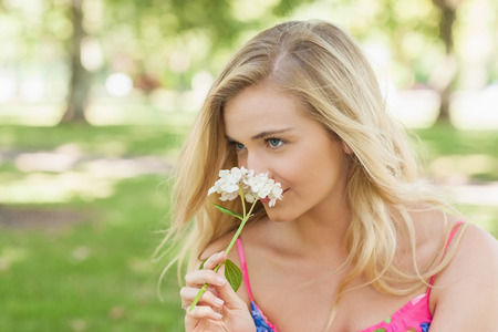 Lovely blonde woman smelling a flower sitting in a park photo