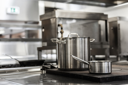 Pots standing on hotplate in professional kitchen Stock Photo