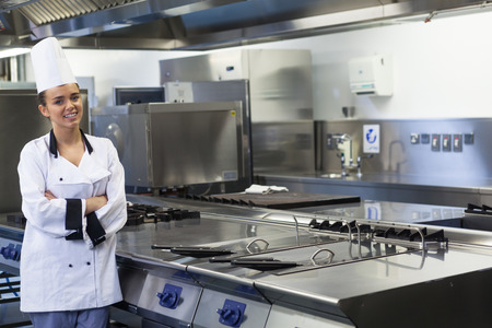 Junge lächelnde Koch stand neben Fläche in der professionellen Küche zu arbeiten