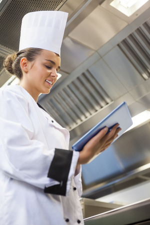 Young content chef using tablet standing in professional kitchen photo